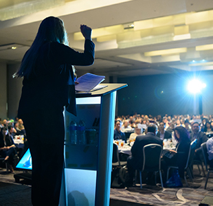 Amie Fishman with fist in air at podium speaking before a crowded auditorium at the 40th Annual NPH Conference
